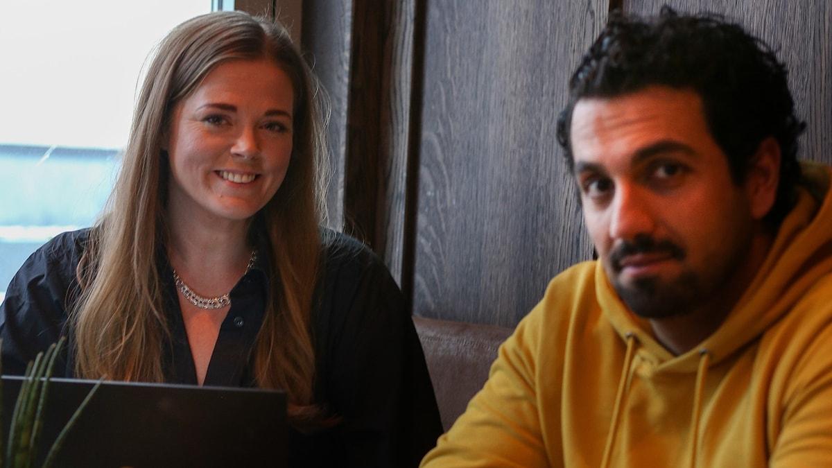 Kvinna med långt, blont hår och man med kort mörkt hår sitter vid ett bord och tittar in i kameran.