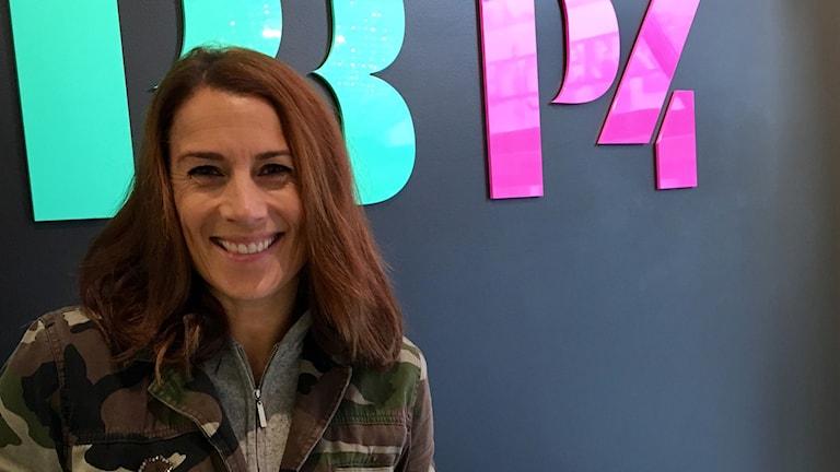 Ansiktsbild på Jill Johnson som står framför en svart vägg med SR:s loggor. Hon har en militärmönstrad jacka på sig.