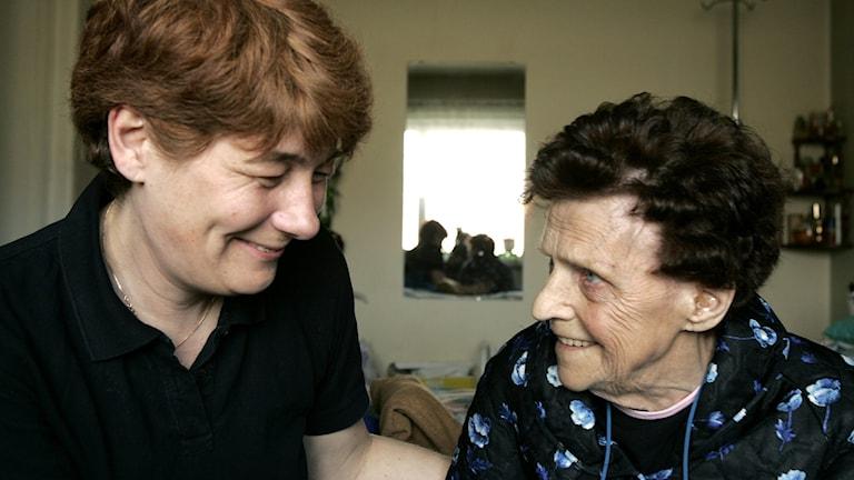 Äldre kvinna ser hemtjänstpersonalen i ögonen och ler.