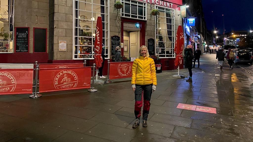 En kvinna står utanför en pub i Edinburgh.