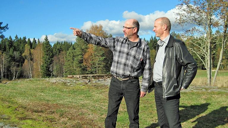 """""""Skandal att det får gå till så här"""". Roy Sjöberg och Svante Hultén tittar ut mot grannfastigheten där bygget av skjutbanan redan är påbörjats. Foto: Joel Wendle."""
