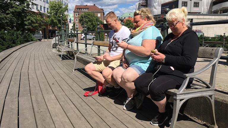 Tre personer sitter på en bänk och tittar ner i sina