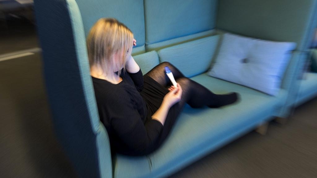 En kvinna sitter i en soffa med ett graviditetstest i handen.