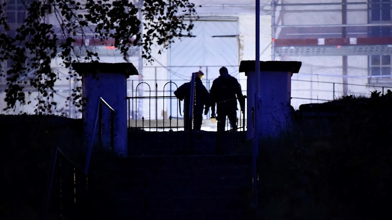 Poliser som går vid Bollebygds Kyrka kvällstid.