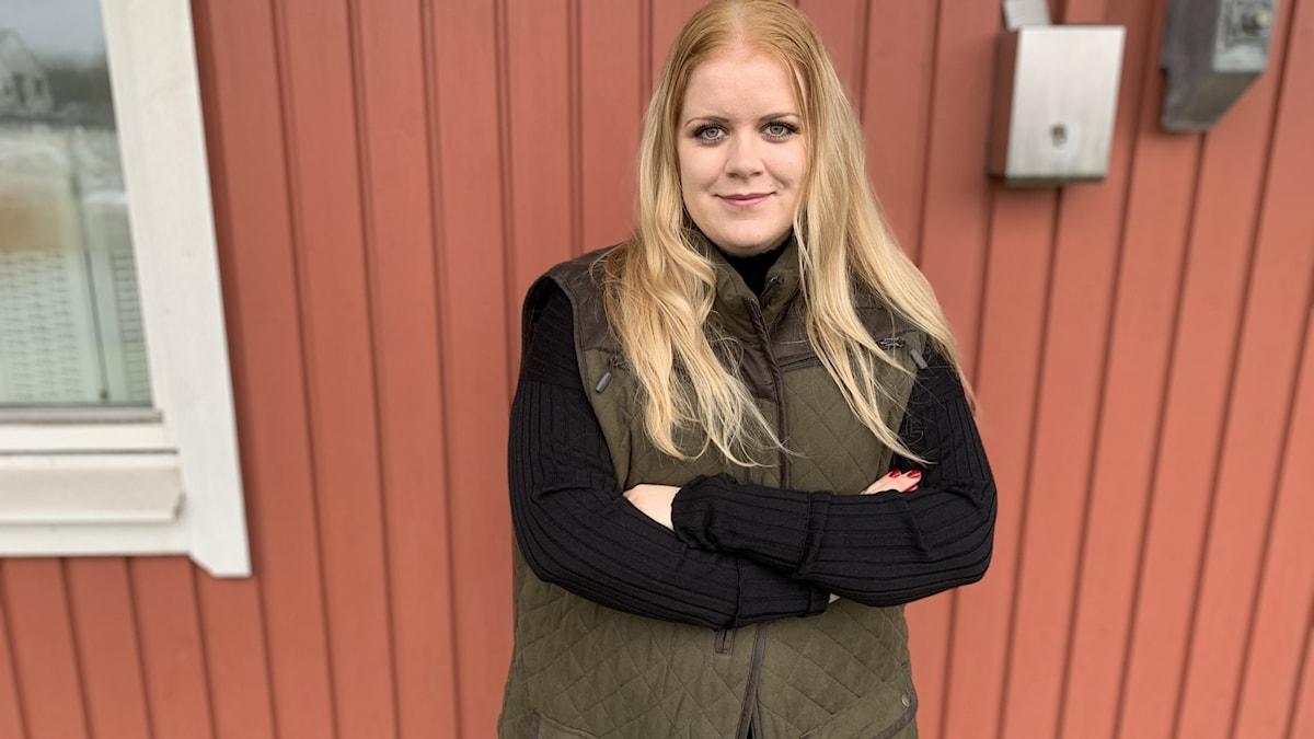 Amanda Fredbrant står mot en röd husvägg.
