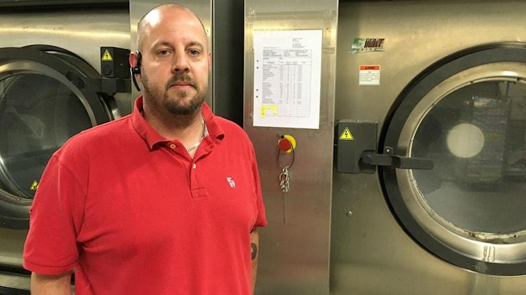 En man i röd t-shirt står framför en industritvättmaskin