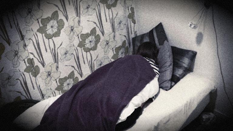 Någon ligger under täcke och filt i en säng. Bilden är suddig och svartvit.