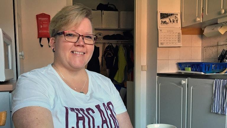 Sari sitter vid sitt köksbord och tittar in i kameran och ler
