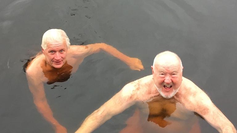 Två män badar i kallvatten och ser glada ut.