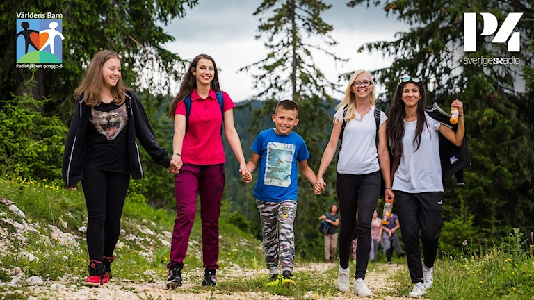 Fem barn går på en skogsväg och håller varann i händerna.