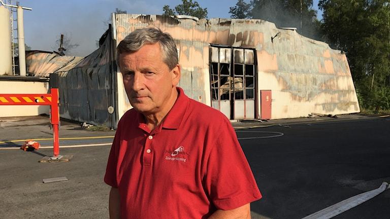 Man i röd skjorta framför sin nedbrunna fabrik.