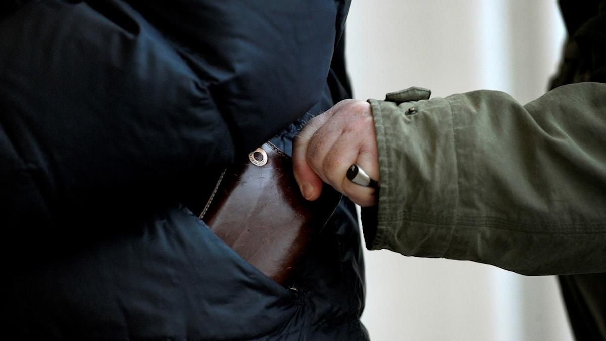 En person tar en plånbok ur en annan persons jackficka.