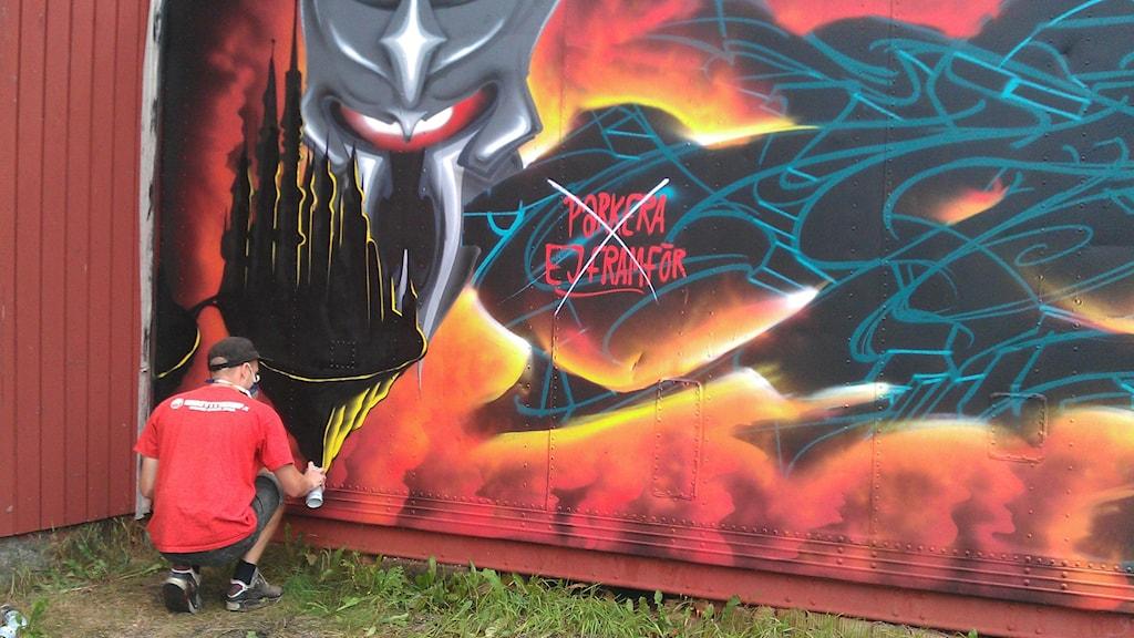 Adam Algotsson i färd med att måla. Foto: Caroline Aronsson/SR