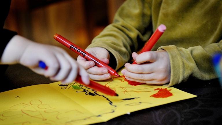 Barn ritar på papper med tuschpennor.