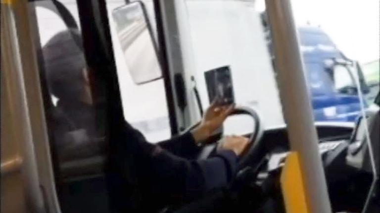 Busschauffören ser på mobilen och kör samtidigt.