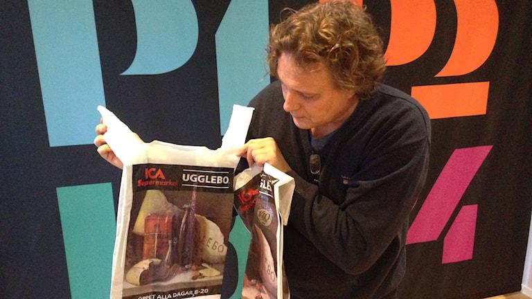 Konstnären Tony Warren med den påse som Ica tryckt utan hans tillstånd. Foto: Erika Larsson/SR.