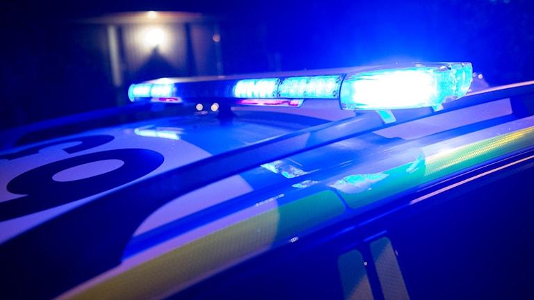 Polisbil med blåljus påslaget i mörker.