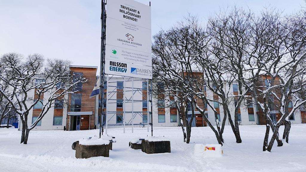 Det renoverade flerbostadshuset på Backgårdsgatan 1 i Vårgårda, med en ställning, med information om att projektet är prisat och miljövänligt, i förgrunden.