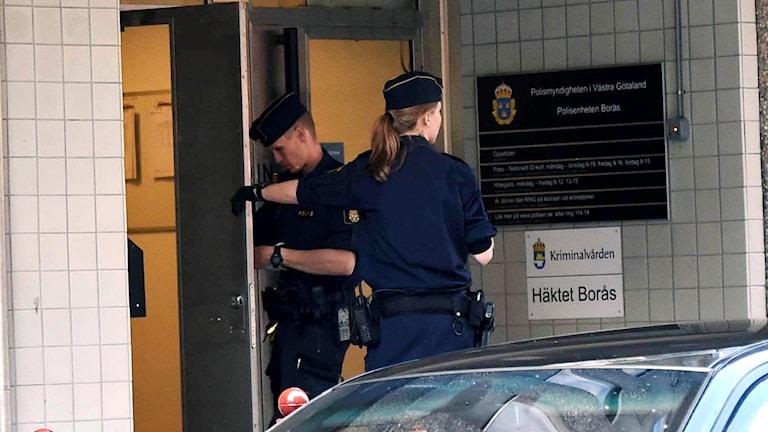 Polisen undersöker skottskadorna på polishusets entrédörr. Foto: Joakim Eriksson/Agena Foto