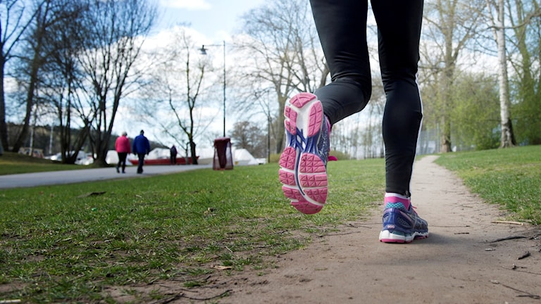 Tjej löper på motionsspår.