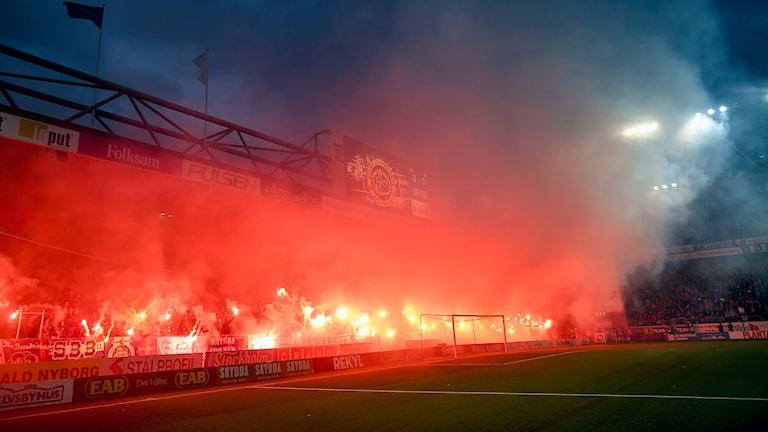 Blåvita supportrar med bengaler och masker under matchen IF Elfsborg och IFK Göteborg. Foto: Björn Larsson Rosvall / TT.