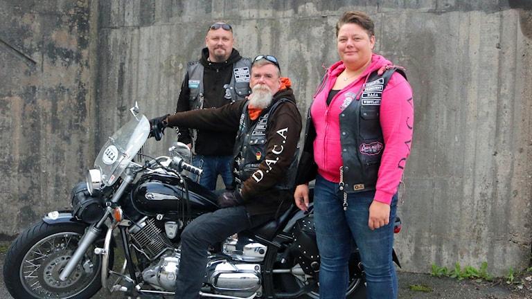 En man sitter på en motorcykel och en annan man och kvinna står bredvid