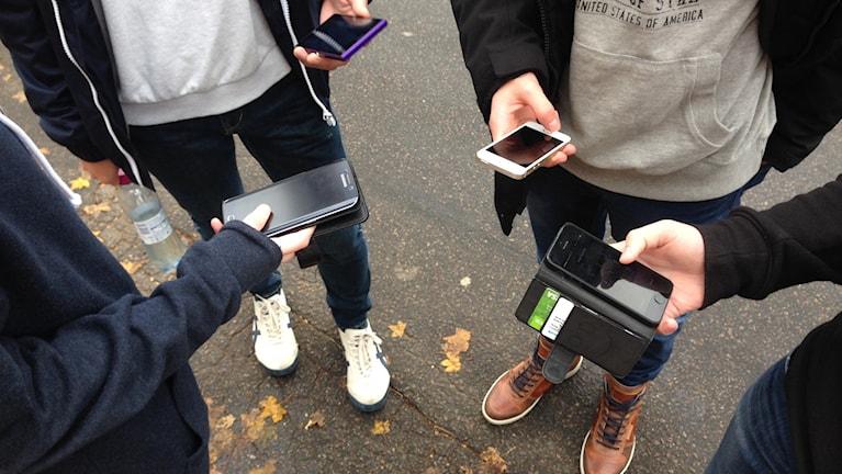 Elever håller mobiltelefoner.