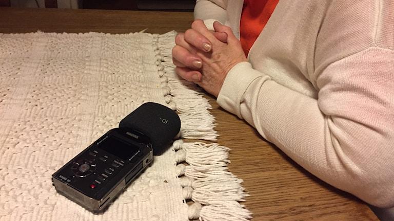 Mikrofon för inspelning av ljud ligger på ett bord och kvinna som sitter med knäppta händer under en intervju.