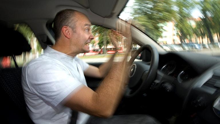Aggressiv körning, arg manlig bilförare kör bil och gestikulerar.