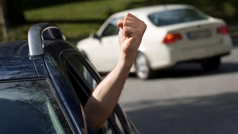 Aggressiv körning, arg manlig bilförare gestikulerar med knuten näve genom bilrutan.