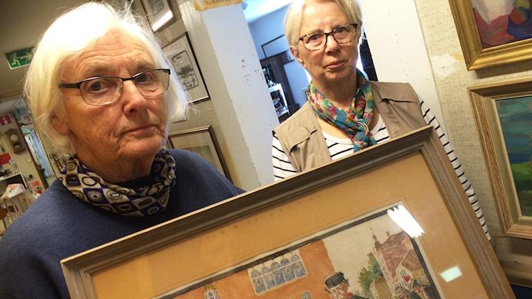 Barbro Sandberg och Gertrud Jonsson Gärdhems secondhand håller i tavlan.