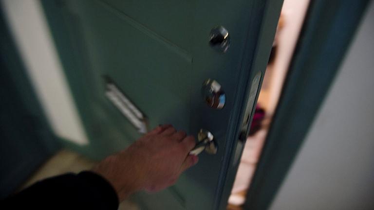 En person öppnar en lägenhetsdörr