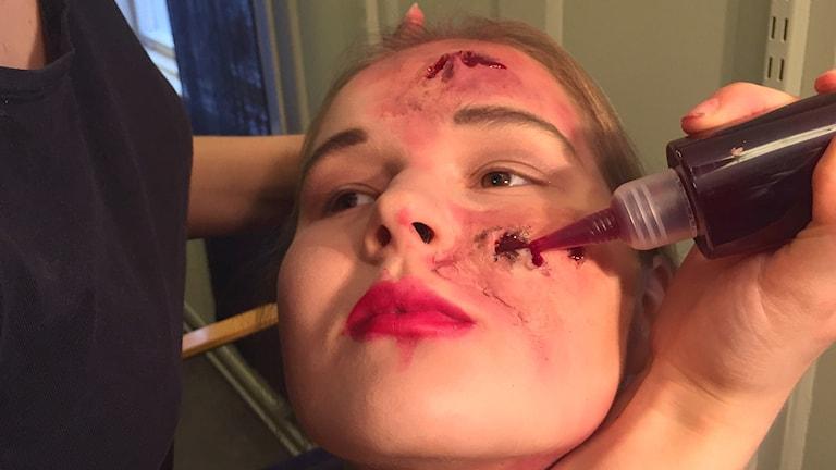 Ansiktsbild på flicka som blir sminkad med en tub så det ser ut som att hon har bild i ansiktet