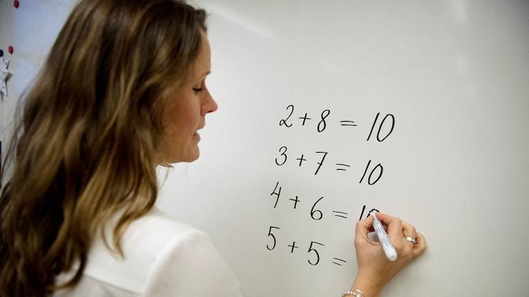 En lärare skriver siffror på tavlan