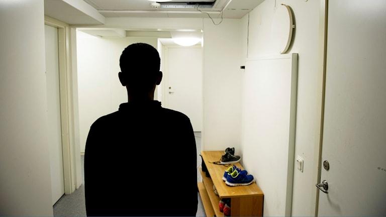 Ett ensamkommande flyktingbarn sedd bakifrån i en hall.