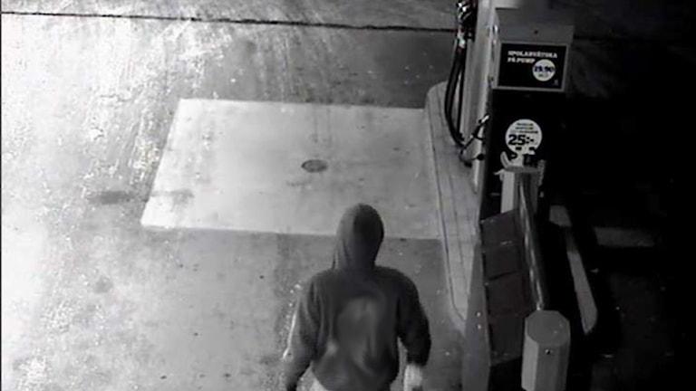 Mannen syns bakifrån filmad av en övervakningskamera på en bensinstation.
