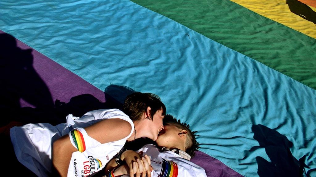 Två lesbiska kvinnor ligger och kysser varandra på en prideflagga.