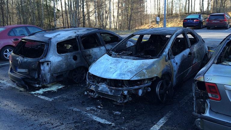Två utbrända bilar på parkeringplatsen.