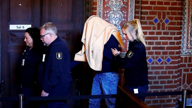 Den åtalade mannen leds till rättegången av väktare.