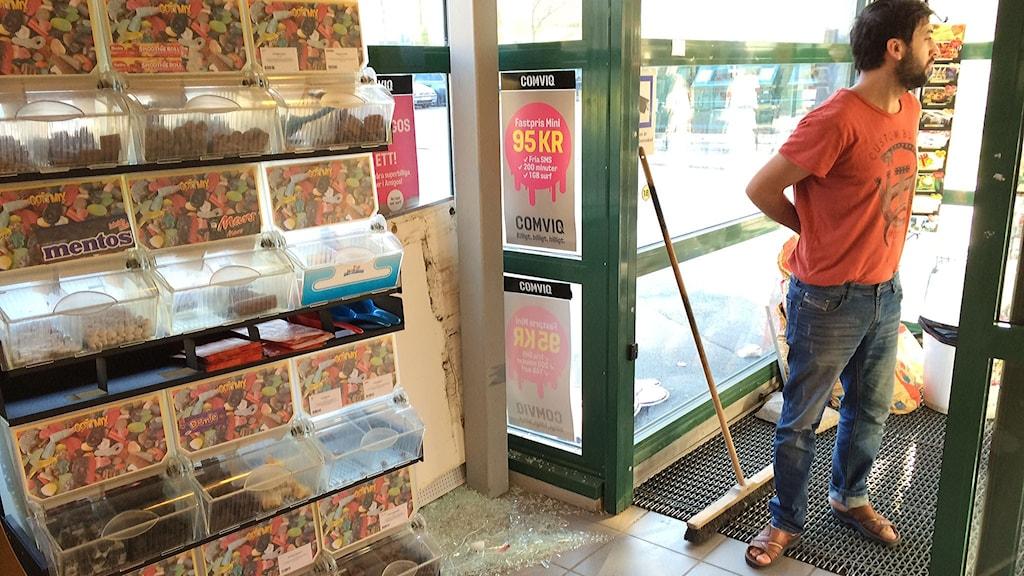 Butiksägaren sopar upp krossat glas i sin butik.