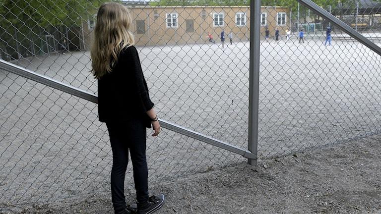 En flicka står bakom ett stängsel och tittar ut över en grusplan där en grupp barn leker på avständ
