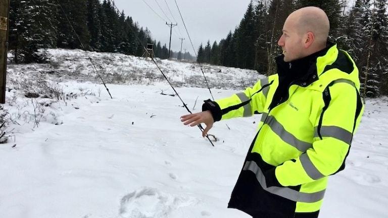 Per Karlsson står iklädd en gul varseljacka framför en mosse i skogen som är täckt med ett tunt lager snö.