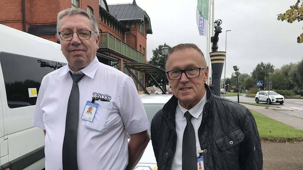 Två män i taxiuniform står utanför Järnvägshuset i Ulricehamn.