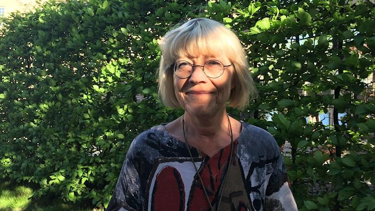 Karin Jageby (V) framför en grönskande häck.