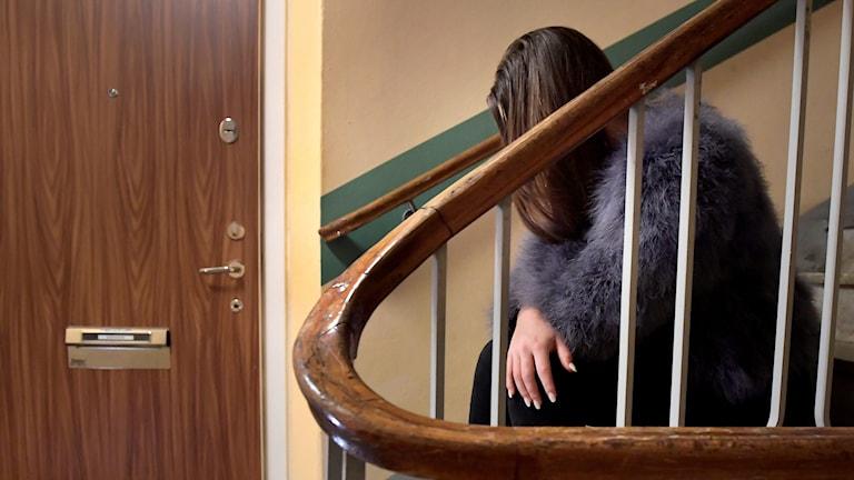 En tonårsflicka sitter i en trappuppgång.