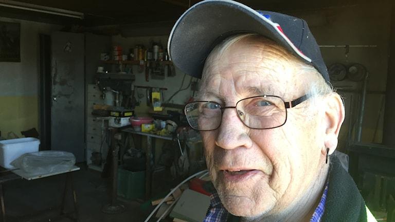 Äldre man i ingången till sitt garage.
