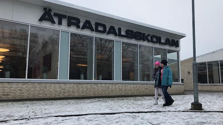 Två barn går förbi entrén på Ätradalsskolan i Timmele.