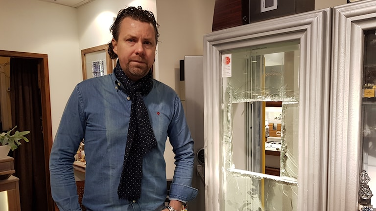 Man med mörkt hår, sjal och jeansskjorta står bredvid en butiksmonter. Montern är trasig. Mannen ser sammanbiten ut.