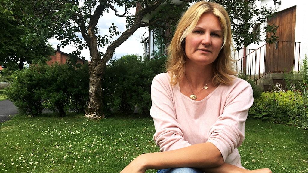 Jenny Wulf sitter till höger i bild, på huk. Bakom henne syns en grön gräsmatta med vita klöverblommor, ett träd och en grön häck.