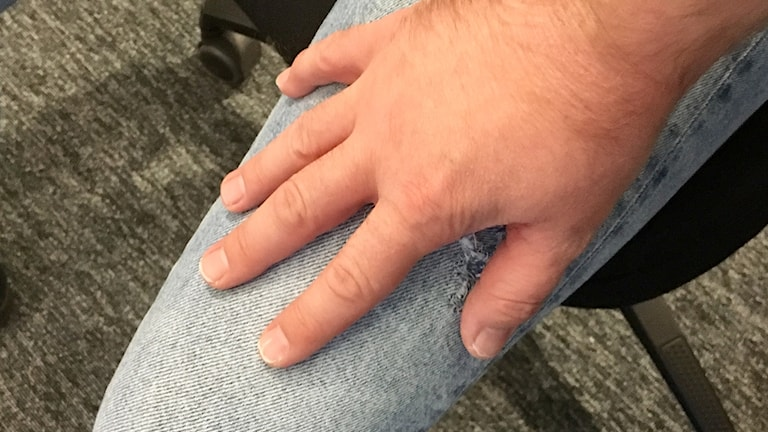 En hand på ett lår